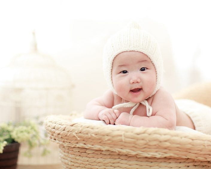 cute baby sitting on a basket smiling
